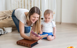 Happy mother reading book to her 10 months old baby boy on floor Stock Images