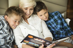 Happy mother reading book to her two sons Royalty Free Stock Photo