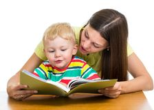Happy mother reading a book to kid Stock Photos