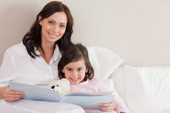 Happy mother reading a story to her daughter Royalty Free Stock Photo