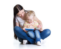 Happy mother reads a book to baby girl isolated on white Stock Photos
