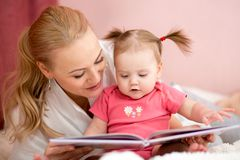 Happy mother reads a book to baby girl Royalty Free Stock Photos