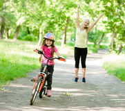 Happy mother rejoices that her daughter learned to ride a bike Stock Image