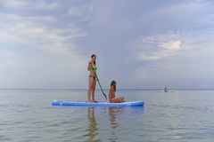 Happy mother rolls her daughter on a Board for SAP surfing on the calm sea. Against the picturesque sky stock photos