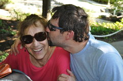 Happy Mother's Day. A men is kissing his mother with tons of love Royalty Free Stock Image