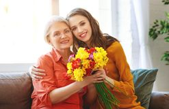 Happy mother`s day! adult daughter gives flowers and congratulates an elderly mother on holiday stock image