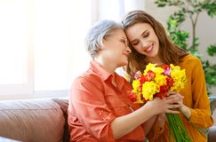 Happy mother`s day! adult daughter gives flowers and congratulates an elderly mother on holiday royalty free stock photos