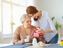 Happy mother`s day! adult daughter gives gift  and congratulates an elderly mother on holiday. Happy mother`s day! adult daughter gives gift and congratulates an stock photos