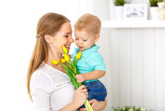 Happy mother`s day. Baby son gives flowers for mom Stock Image