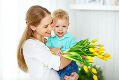 Happy mother`s day. Baby son gives flowers for mom. Happy mother`s day. Baby son congratulates mom, gives her flowers royalty free stock photo
