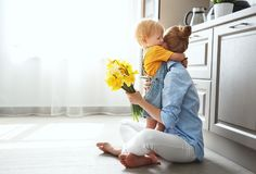 Happy mother`s day! baby son gives flowersfor mother on holiday. Happy mother`s day! baby son congratulates mother on holiday and gives flowers Royalty Free Stock Image