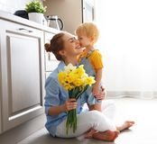 Happy mother`s day! baby son gives flowersfor mother on holiday. Happy mother`s day! baby son congratulates mother on holiday and gives flowers royalty free stock photography