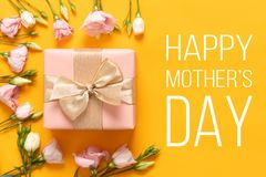 Happy Mother`s Day Background. Bright Yellow and Pastel Pink Colored Mother Day Background. Flat lay greeting card with gift box.