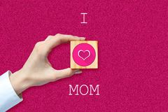 Happy Mother`s Day background. Female hand with social heart icon. Pink background. Congratulatory background. Festive background royalty free stock photo