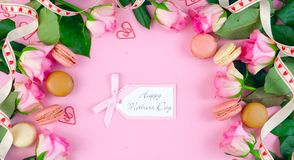 Mother`s Day background of pink roses and macaron cookies on pink wood table. Stock Photos