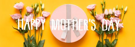 Happy Mother`s Day Banner. Bright Yellow and Pastel Pink Colored Mother Day Banner. Flat lay greeting card with beautiful gift box. And pink lisianthus flowers stock photos