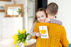 Happy Mother`s Day or Birthday Background. Adorable young girl giving her mom, young cancer patient, homemade I LOVE MOM card. royalty free stock image