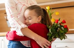 Happy Mother`s Day or Birthday Background. Adorable young girl hugging her mom after surprising her with bouquet of red roses. royalty free stock photography