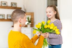 Happy Mother`s Day or Birthday Background. Adorable young girl surprising her mom with bouquet of tulips. Family celebration. royalty free stock photos