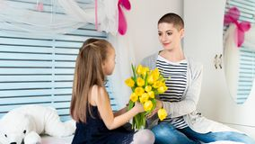 Happy Mother`s Day or Birthday Background. Adorable young girl surprising her mom with bouquet of yellow tulips. Family celebration concept royalty free stock photo