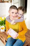 Happy Mother`s Day or Birthday Background. Adorable young girl surprising her mom, young cancer patient, with bouquet and present. stock photo