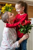 Happy Mother`s Day or Birthday Background. Adorable young girl surprising her mom, young cancer patient, with bouquet of red roses royalty free stock photos