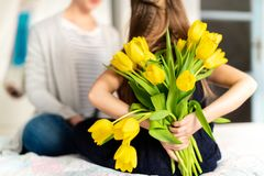 Happy Mother`s Day or Birthday Background. Unrecognizable young girl surprising her mom with bouquet of yellow tulips. Family celebration concept royalty free stock image