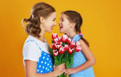 Happy mother`s day! child daughter gives mother a bouquet of flowers on color yellow background royalty free stock images