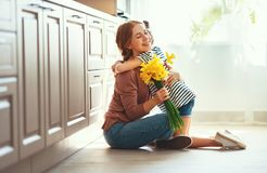 Happy mother`s day! child daughter   gives mother a bouquet of flowers to narcissus and gift. Happy mother`s day! child daughter congratulates mother and gives a royalty free stock photography