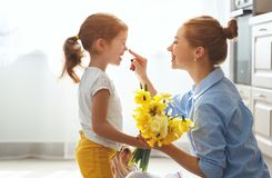 Happy mother`s day! child daughter   gives mother a bouquet of f. Happy mother`s day! child daughter congratulates mother and gives a bouquet of flowers to Stock Photos