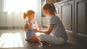 Happy mother`s day! child daughter congratulates her mother and. On  floor in kitchen read postcard Royalty Free Stock Photo