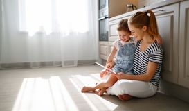 Happy mother`s day! child daughter congratulates her mother and. On floor in kitchen read postcard stock image