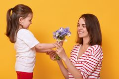 Happy mother`s day! Child daughter congratulates mom and gives her bouquet of flowers. Mum wearing striped shirt and little girl royalty free stock photography