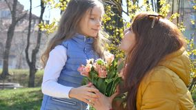 Happy mother`s day. Child daughter congratulates mom and gives her a flowers. Mum and girl smiling and hugging. Family stock footage