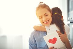 Happy mother`s day! Child daughter congratulates moms and gives Stock Images