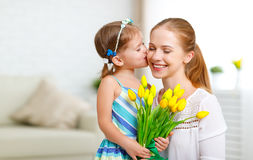 Happy mother`s day! Child daughter congratulates moms and gives. Her a postcard and flowers tulips Stock Photography