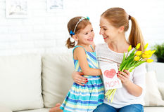 Happy mother`s day! Child daughter congratulates moms and gives Royalty Free Stock Photos