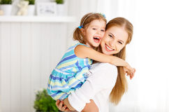 Happy mother`s day! Child daughter congratulates moms and gives. Her a postcard and flowers tulips Stock Photo