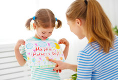 Happy mother`s day! Child daughter congratulates moms and gives Royalty Free Stock Photo