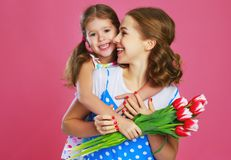 Happy mother`s day! child daughter gives mother a bouquet of flowers on color pink background stock photography