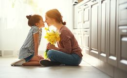 Happy mother`s day! child daughter   gives mother a bouquet of flowers to narcissus and gift royalty free stock images