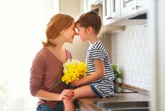 Happy mother`s day! child daughter   gives mother a bouquet of flowers to narcissus and gift. Happy mother`s day! child daughter congratulates mother and gives a stock image