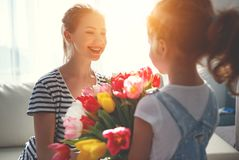Happy mother`s day! child daughter gives mother a bouquet of f. Happy mother`s day! child daughter congratulates mother and gives a bouquet of flowers to tulips stock images