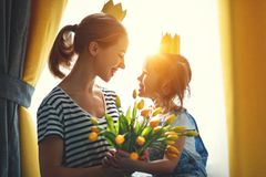 Happy mother`s day! mother and child daughter in crowns and with. Flowers yellow tulips stock images