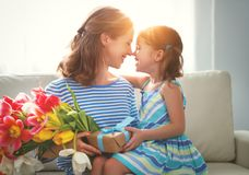 Happy mother`s day! child daughter   gives mother a bouquet of f. Happy mother`s day! child daughter congratulates mother and gives a bouquet of flowers to Stock Photo