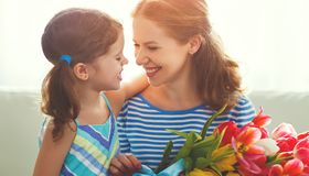 Happy mother`s day! child daughter gives mother a bouquet of f. Happy mother`s day! child daughter congratulates mother and gives a bouquet of flowers to tulips royalty free stock images