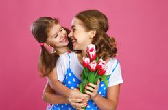 Happy mother`s day! child daughter gives mother a bouquet of flowers on color pink background. Happy mother`s day! child daughter congratulates mother and gives royalty free stock photos