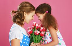Happy mother`s day! child daughter gives mother a bouquet of flowers on color pink background stock image