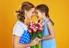 Happy mother`s day! child daughter gives mother a bouquet of flowers on color yellow background royalty free stock photos