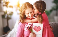 Happy mother`s day! child daughter gives mother a bouquet of flowers and postcard. Happy mother`s day! child daughter congratulates mother and gives a bouquet of royalty free stock photo